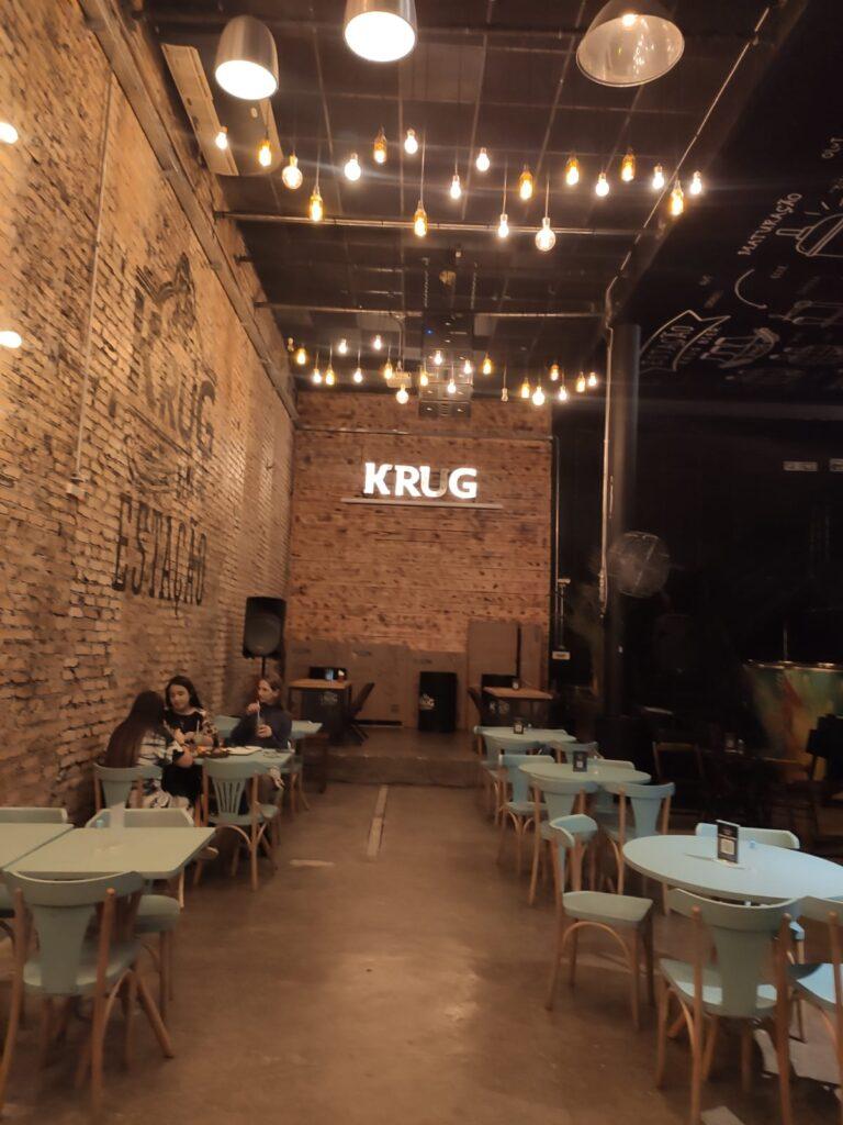 No ambiente interno da Estação Krug Bier se misturam linhas industriais e rústicas na decoração despojada